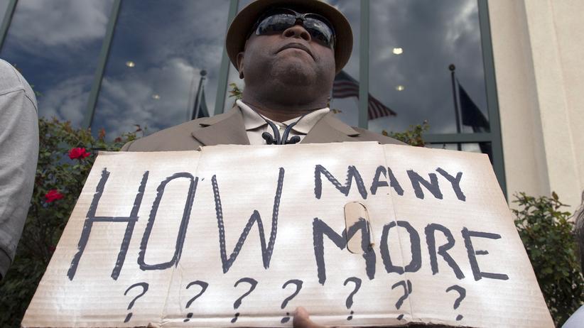 """Reverend Arthur Prioleau aus Goose Creek, South Carolina, hält ein Schild mit der Aufschrift: """"Wie viele noch?"""""""