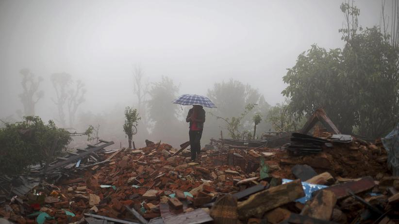 Nepal: Ein Bewohner geht im Schutz eines Regenschirms über verwüstetes Gelände in einem Dorf in der nepalesischen Region Gorkha.
