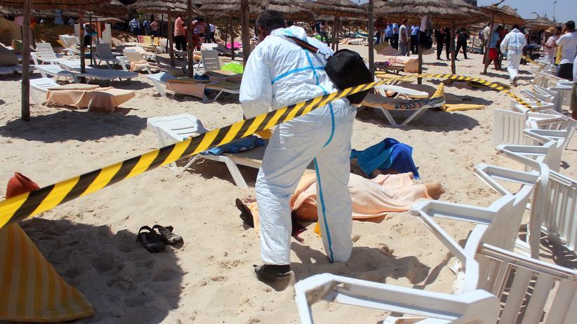 Anschlag in Tunesien: Ein Polizist untersucht den Strand, an dem ein Attentäter mehrere Menschen erschossen hat.