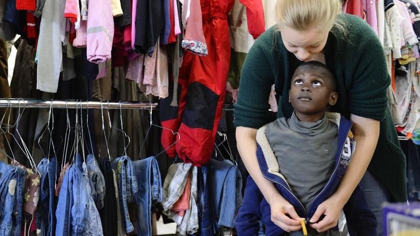 """Helferin und Flüchtlingskind in der Kleiderkammer der """"Bayernkaserne"""""""