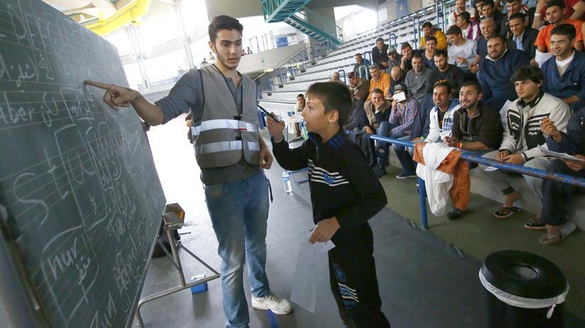 Ein Helfer gibt Flüchtlingen in Hanau Deutschunterricht. (Archivbild)