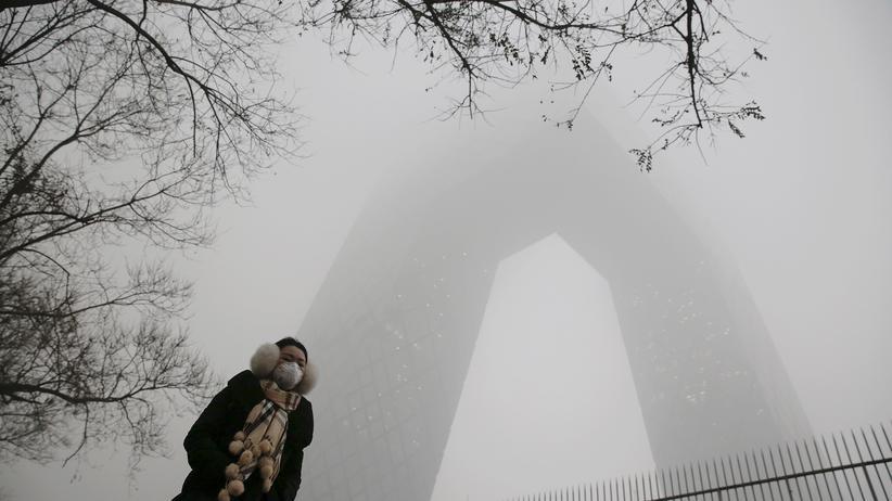 China: Eine Frau geht mit einer Atemschutzmaske vor dem Hauptquartier des chinesischen Staatssenders CCTV durch Peking.