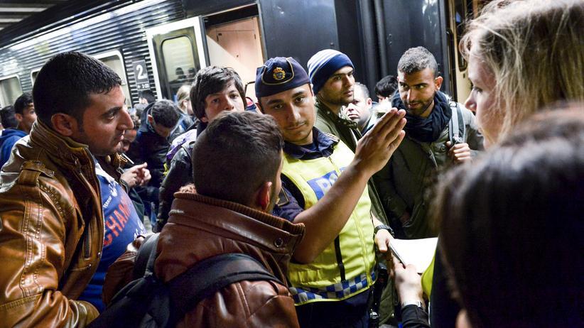 Flüchtlinge bekommen im September 2015 im Stockholmer Bahnhof Anweisungen von einem Polizisten.