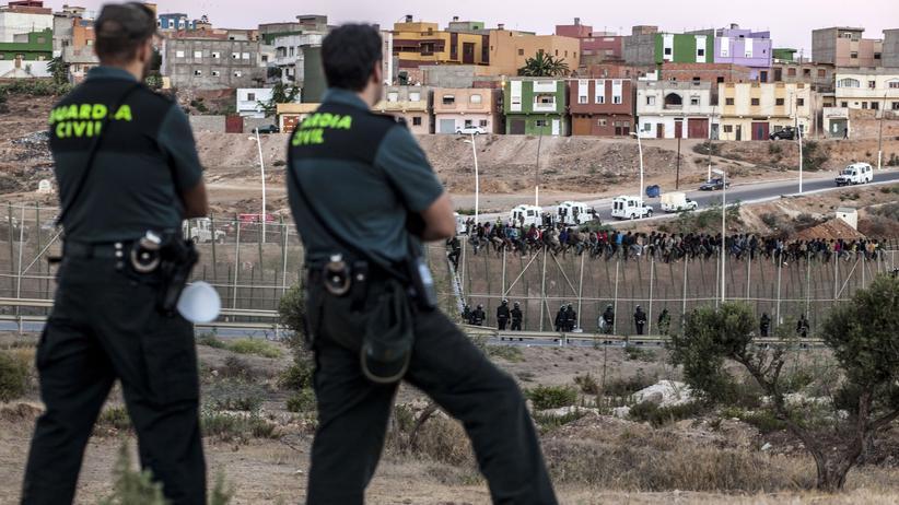 Flüchtlinge: Spanische Polizisten beobachten Flüchtlinge, die auf dem letzten Grenzzaun gestoppt wurden.