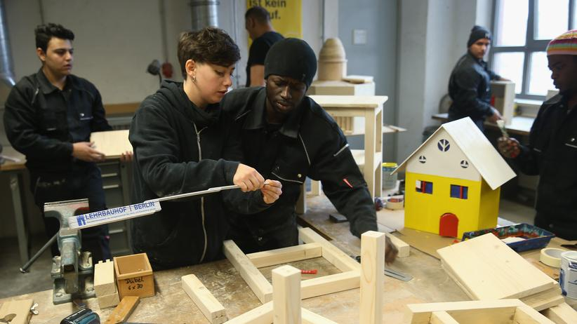 "Flüchtlingshilfe: BERLIN, GERMANY - DECEMBER 17: Instructor Mona Nasser (L) helps asylum-applicant Ala Hage from Gambia as asylum-seekrs from countries including Lebanon, syria and Kosovo work on prjects in the cabinet-making tradecrafts exposure program at the Arrivo center on December 17, 2015 in Berlin, Germany. The Arrivo program, under the slogan ""Refugee is not a job,"" offers asylum-applicants two-week exposure courses to a variety of tradecrafts, including cabinet making, auto mechanics and baking, as well as German-language instruction. Arrivo partners with the German association of skilled crafts (Zentralverband des deutschen Handwerks) and helps refugees and migrants to continue their training by finding apprenticeships and job training. Germany is likely to receive over one million migrants and refugees this year and the German government is eager to integrate those who stay into the workforce. (Photo by Sean Gallup/Getty Images)"