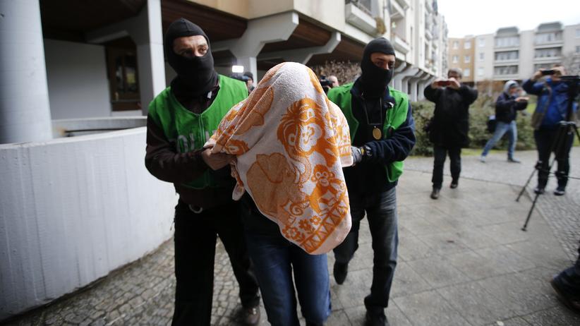 """""""Islamischer Staat"""": Polizisten führen einen der verdächtigen Islamisten in Berlin-Kreuzberg ab"""