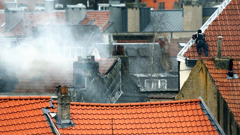 Brüssel: A masked Belgian policeman secures the area from a rooftop above the scene where shots were fired during a police search of a house in the suburb of Forest near Brussels, Belgium, March 15, 2016. Teargas is seen at left. REUTERS/Francois Lenoir TPX IMAGES OF THE DAY - RTSAKO1