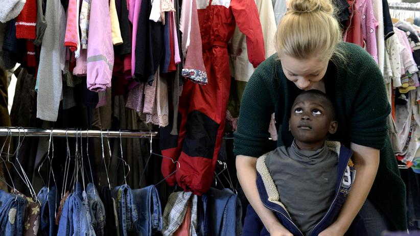 Flüchtlingsbetreuung: Eine Helferin mit einem Flüchtlingsjungen in einer Kleidersammelstelle