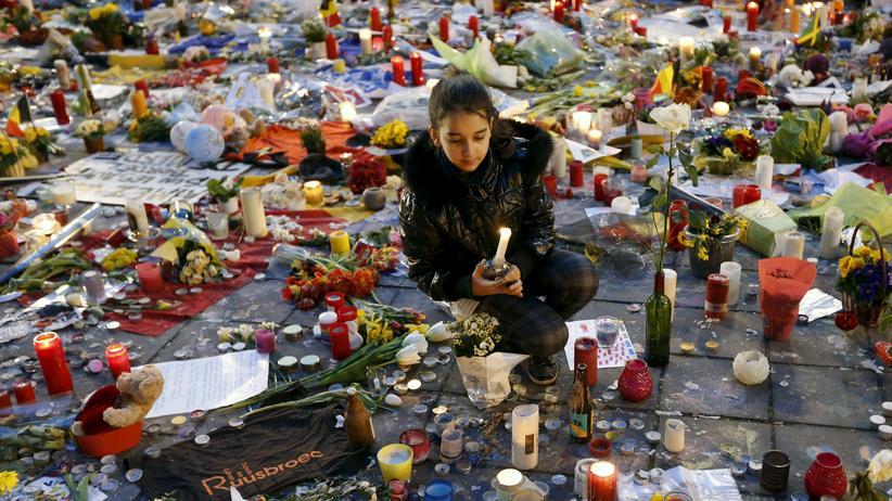Terror und Medien: Ein Mädchen entzündet eine Kerze auf dem Börsenplatz in Brüssel, wo viele Belgier der Opfer der jüngsten Terroranschläge gedenken.