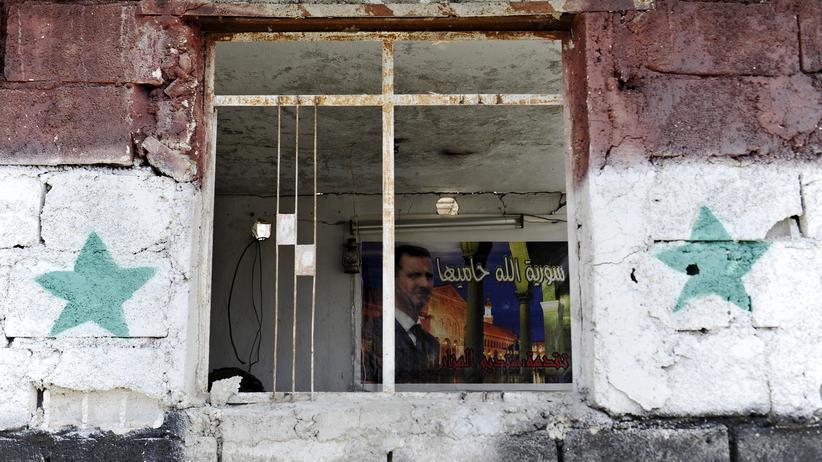 Ein Radfahrer fährt an zerstörten Gebäuden in Homs entlang.