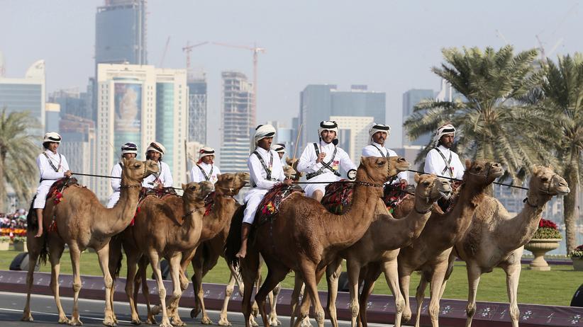 Polizisten reiten auf Kamelen durch Katar.
