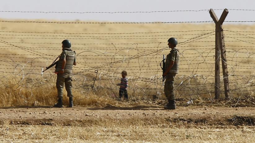 Syrisch-türkische Grenze: Türkische Soldaten und ein Flüchtlingskind an der Grenze zu Syrien nahe der Stadt Akcakale im Südosten der Türkei