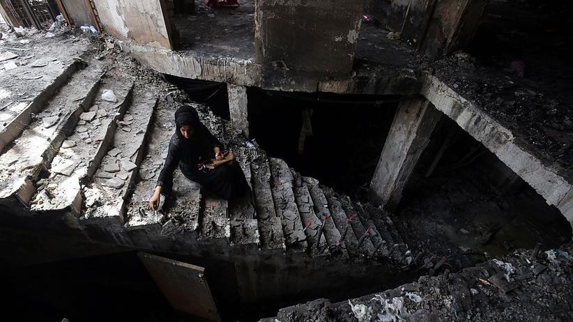 Irak: Eine Irakerin zündet Kerzen in der Ruine des Einkaufszentrums an, das IS-Extremisten am 3. Juli angegriffen hatten (Archiv). Zum Attentat in Balad lagen zunächst keine Fotos vor.