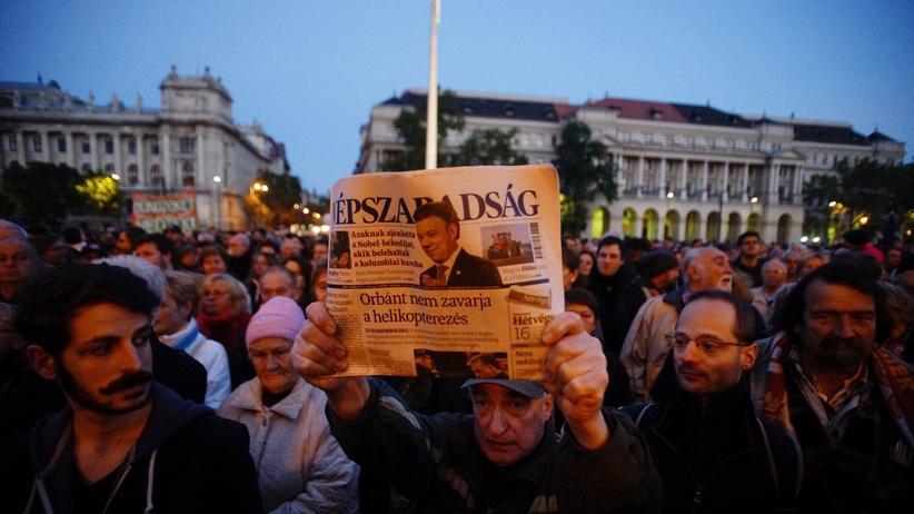 """Ungarn: Bei einem Protest gegen die Einstellung von """"Népszabadság"""" hält ein Demonstrant in Budapest die letzte gedruckte Ausgabe der ungarischen Oppositionszeitung hoch."""