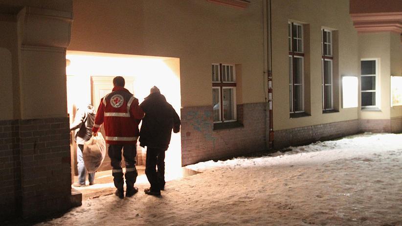 Obdachlose im Winter: Ein Helfer des Roten Kreuzes bringt in Berlin einen Obdachlosen in eine wärmende Unterkunft.