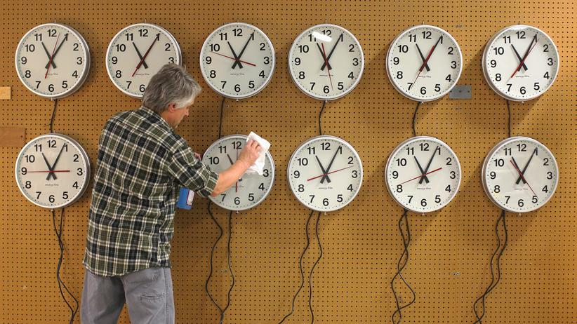 EIn Mitarbeiter reinigt Uhren, die in einem Restaurant in Massachusetts aufgehängt werden sollen