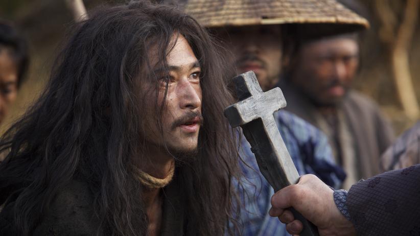 """""""Silence"""": Dramatische Szene aus Martin Scorseses Film """"Silence"""": Der japanische Christ Kichijiro (Yosuke Kubozuka) wird von den Schergen des Inquisitors gezwungen, das Kruzifix zu bespucken und seinem Glauben abzuschwören."""