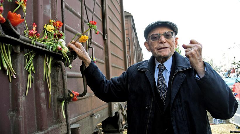 Holocaust: Der Holocaust-Überlebende Heinz Kunio befestigt eine Blume an einem Eisenbahnwaggon, der in Thessaloniki an die Deportation von Juden aus der Stadt erinnert.