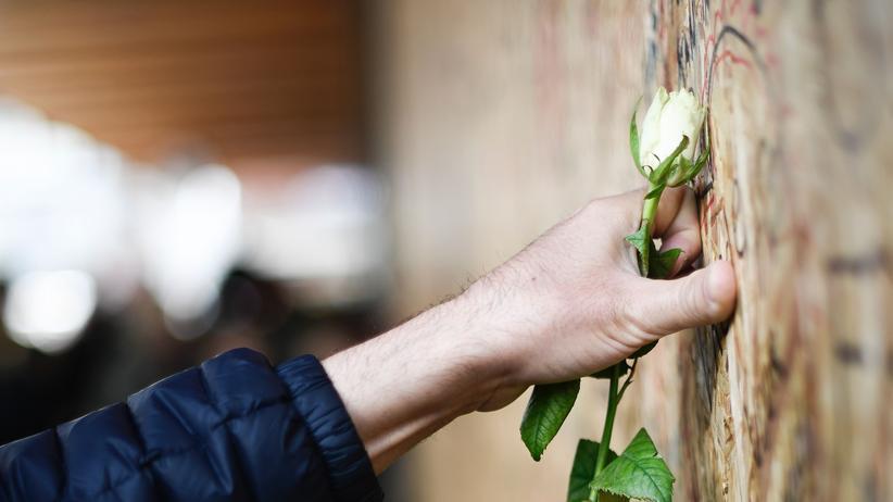 Anschlag in Stockholm: Ein Mann bringt eine Rose zu einer Gedenkwand am Ort des Anschlags in Stockholm