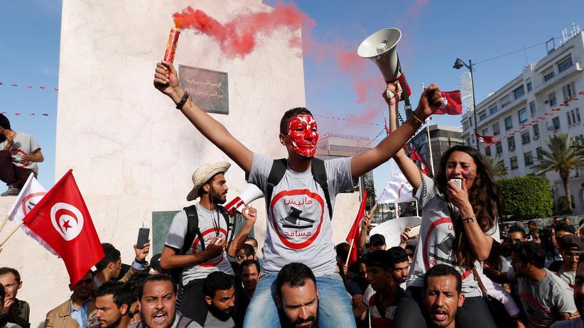 Tunesien: Demonstranten halten Fahnen bei den Protesten gegen das Korruptionsgesetz.