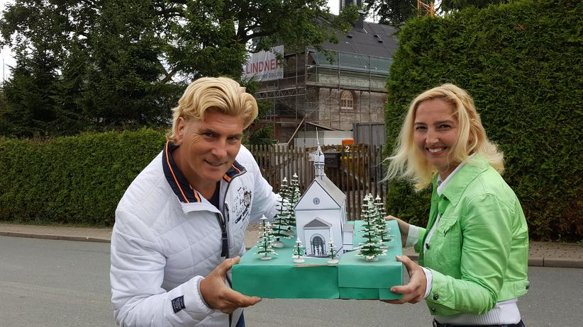 Atheism: Tino and Vivienne Taubert show a model of their church in front of the nearly completed building.