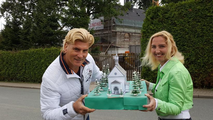 Atheismus: Vivienne und Tino Taubert mit dem Modell ihrer Kirche, das fast fertige Original im Hintergrund