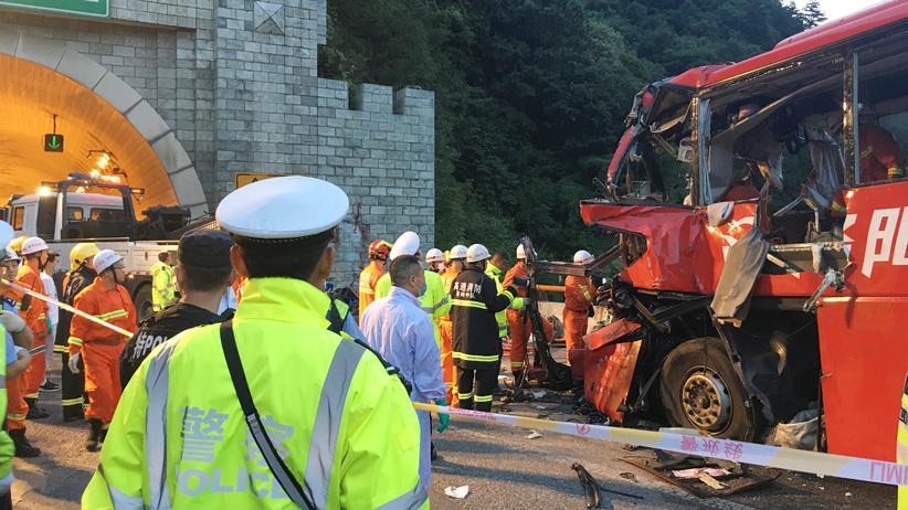 China: Rettungskräfte stehen neben dem schwer beschädigten Bus.
