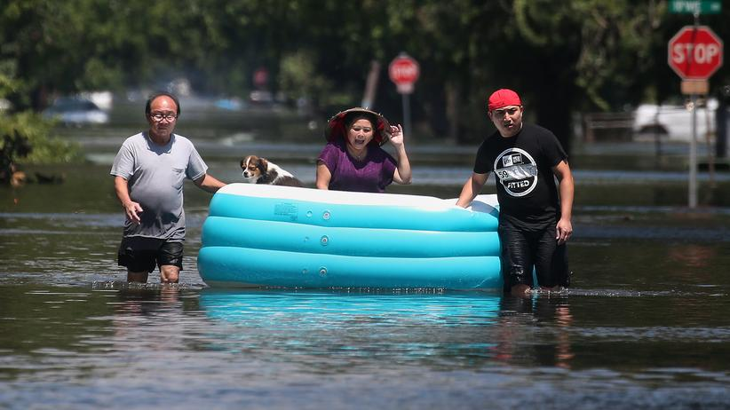 Überschwemmungen in den USA: Menschen benutzen ein Schlauchboot, um ihre Habseligkeiten aus einem überfluteten Gebiet zu transportieren.