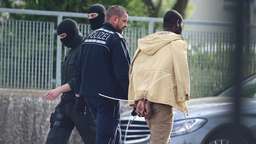 Ellwangen: Vor der Flüchtlingsunterkunft in Ellwangen führt ein Polizist einen festgenommenen Asylbewerber ab.