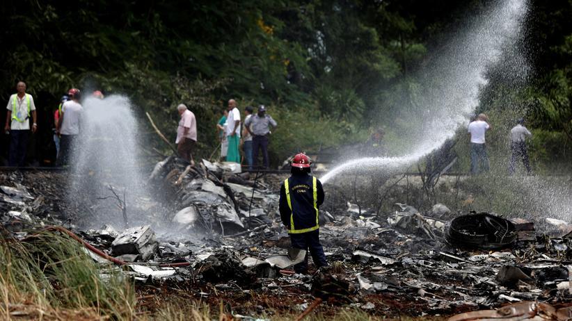 Flugzeugabsturz in Kuba: Ein Feuerwehrmann vor Wrackteilen des abgestürzten Flugzeugs
