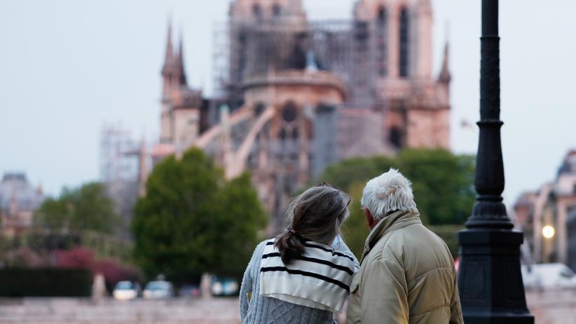Brand in Notre-Dame: Passanten blicken am Dienstagmorgen auf die Kathedrale Notre-Dame. Der Brand ist zu diesem Zeitpunkt noch nicht vollständig gelöscht.