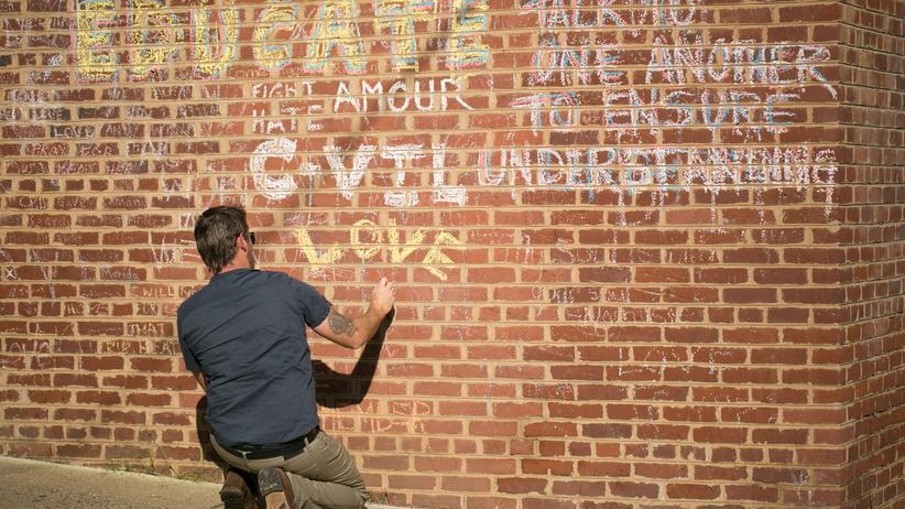 James Fields: Ein Mann malt 2018 eine Nachricht mit Kreide an die Wand in Charlottesville, wo Heather Heyer vor zwei Jahren getötet wurde.