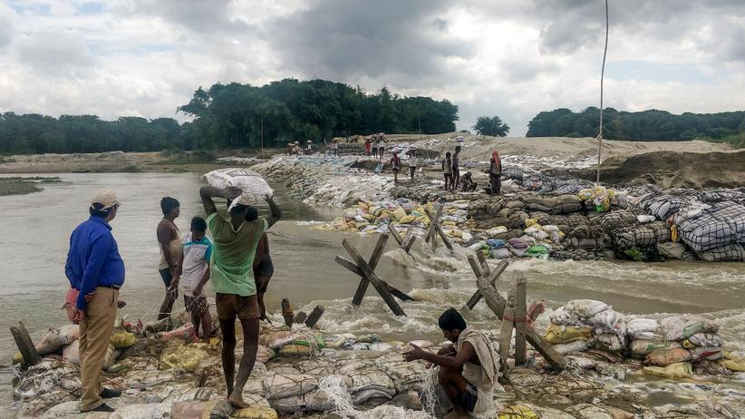 Südasien: Menschen in Indien versuchen, sich mit Sandsäcken gegen die Wassermassen zu schützen.