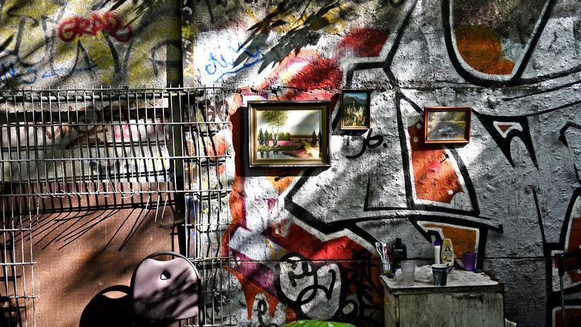 Wohnungsnot: Persönliche Gegenstände eines Obdachlosen vor einem Teilstück der ehemaligen Berliner Mauer