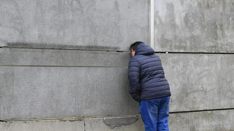 Ostdeutsche Identiät: Ein Tourist an einem Überrest der Berliner Mauer