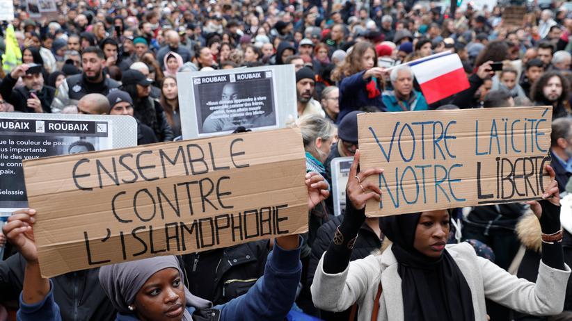 """Paris: """"Zusammen gegen die Islamfeindlichkeit"""" und """"Eure Laizität, unsere Freiheit"""" – zwei Teilnehmerinnen der Pariser Demonstration halten Plakate in die Höhe."""
