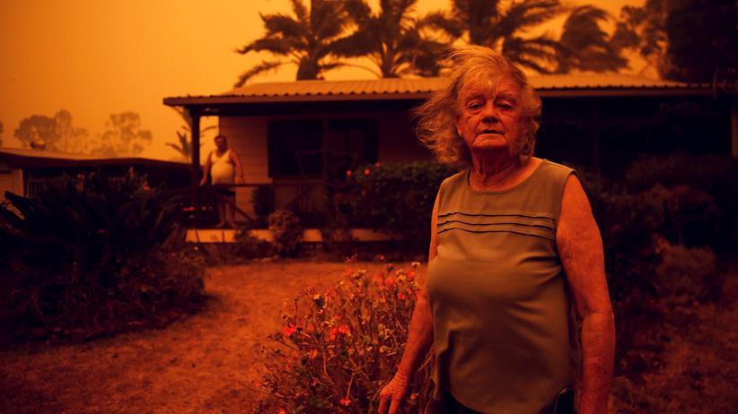 Waldbrände in Australien: Nowra in New South Wales am 4. Januar 2020. Nancy Allen steht vor ihrem Haus im Smog. Auf der Veranda ihr Mann.
