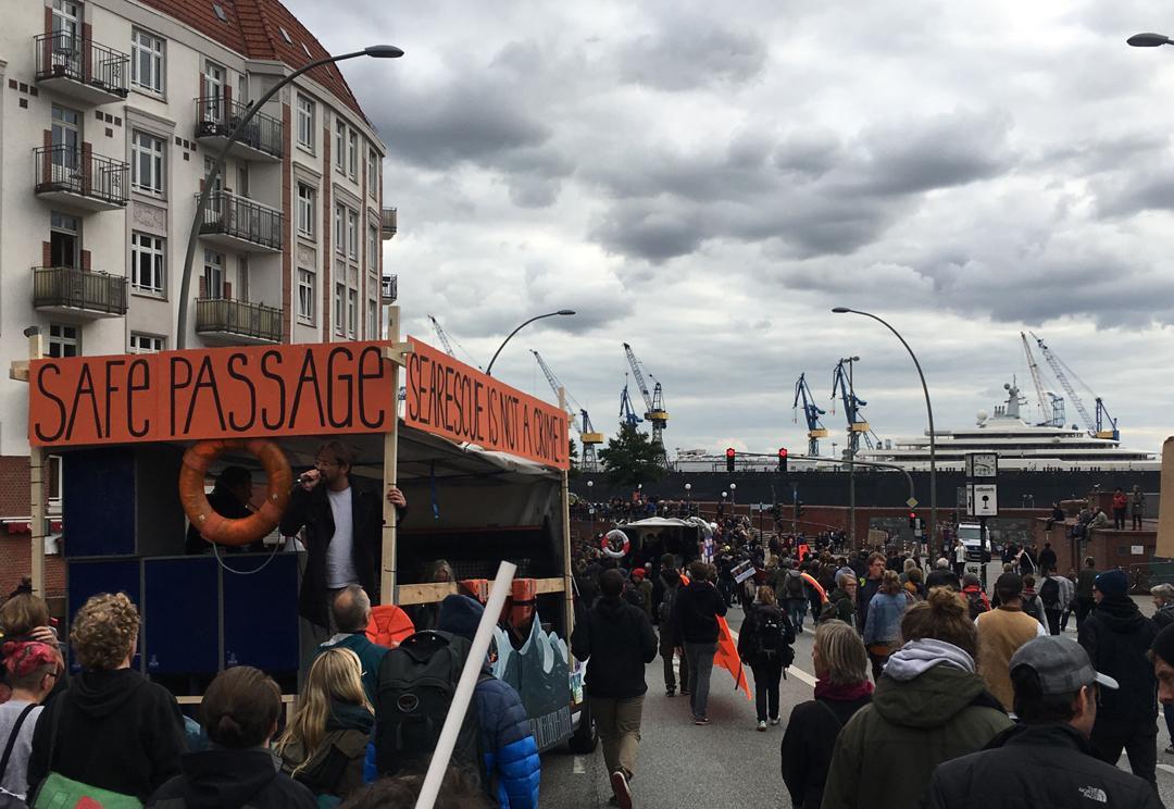 Hamburg – ein sicherer Hafen. Wenn denn das Schiff groß genug ist. Beispielsweise so groß wie die »Eclipse«, die zweitlängste Jacht der Welt, die (hier im Hintergrund zu sehen) gerade bei Blohm+Voss im Trockendock 11 liegt. Aufgenommen wurde das Foto passenderweise bei der Parade »United against Racism« am Sonnabend.