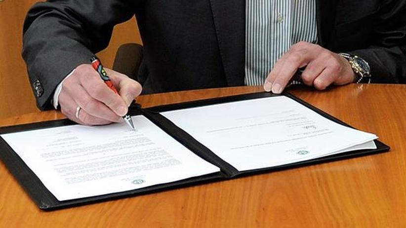 Ein Mann unterzeichnet einen Vertrag