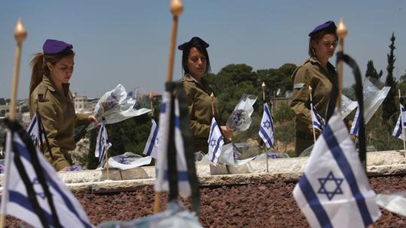 Drei israelische Soldatinnen legen zum Gedenken an den Unabhängigkeitskrieg im Jahr 1948 Blumen auf einem Militärfriedhof nieder