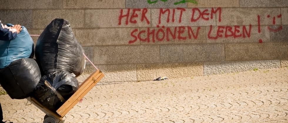 """Graffitti mit dem Schriftzug: """"Her mit dem schönen Leben!"""" auf einer Wand"""