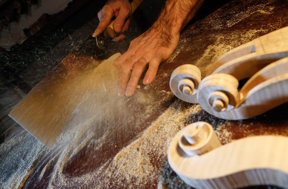 Mit einer Handsäge bearbeitet Menanteau das Holz, um daraus den Wirbelkasten einer Violine zu formen.