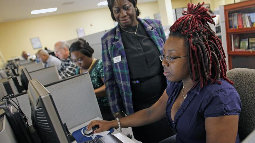 Eine Frau füllt eine Online-Bewerbung in einer Jobagentur in West Palm Beach in Florida aus, eine Arbeitsberaterin unterstützt sie dabei.