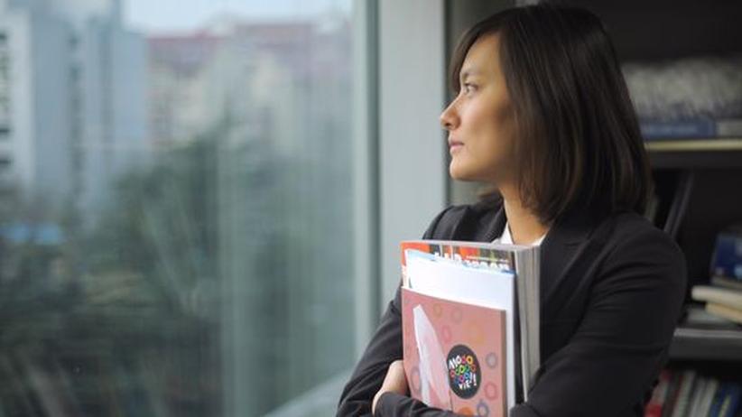 Eine Frau sieht aus dem Fenster von ihrem Büro