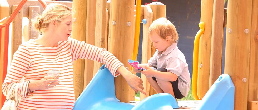 Mutter mit Kind auf einem Spielplatz