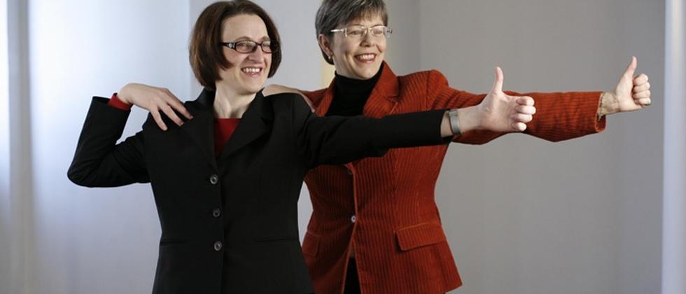 Die beiden Yogalehrerinnen Ulrike Reiche (r.) und Dagmar Völpel zeigen eine Yoga-Übung. Dabei tragen sie normale Bürokleidung