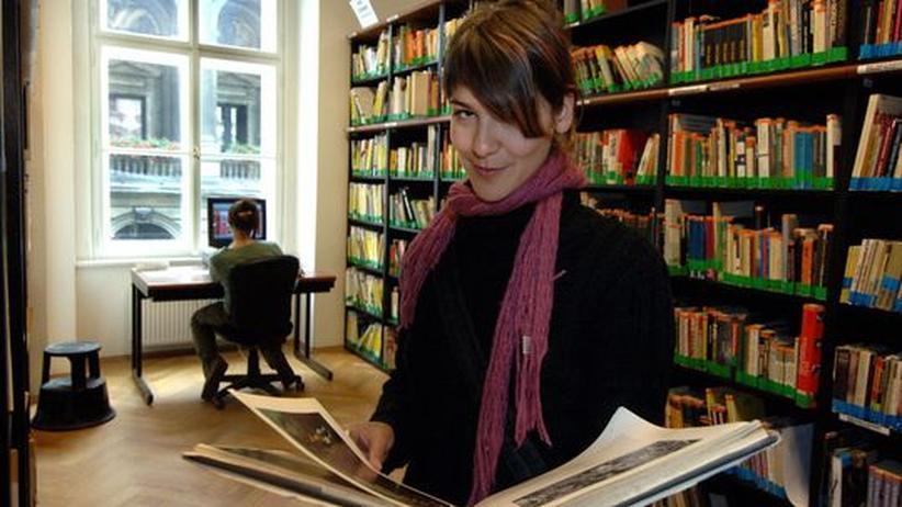 Eine Studentin blättert in einem Buch in einer Bibliothek