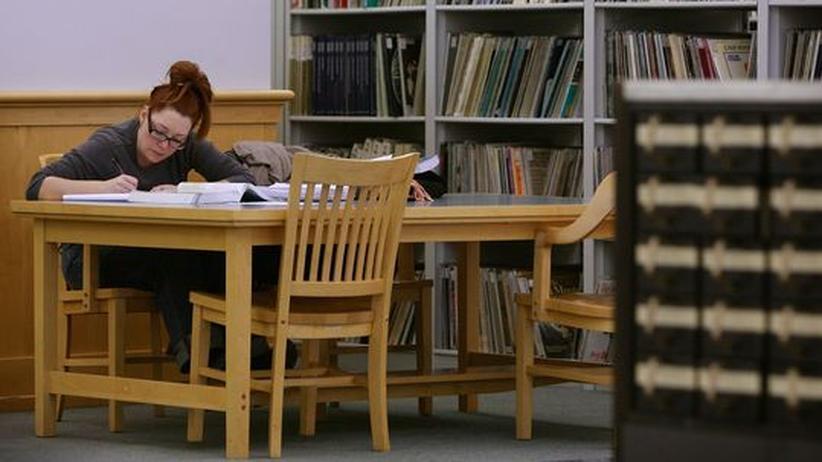 Eine Frau arbeitet sich durch mehrere Bücher