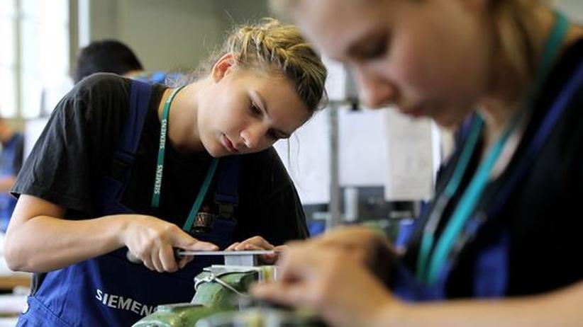 Zwei junge Frauen arbeiten an einer Maschine