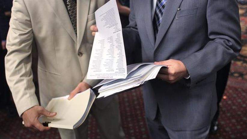 Anpassungsdruck: Ein perfekter Lebenslauf? Ein Personalmanager (rechts) prüft auf einer Jobmesse in Denver, Colorado, die Unterlagen eines Bewerbers